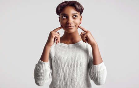 Portrait of young beautiful hipster black girl with short hair smiling in white sweater isolated on white background. Studio shoot.