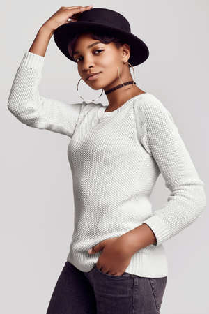 Portrait of young beautiful hipster black girl with short hair smiling in white sweater and fashion hat isolated on white background. Studio shoot.