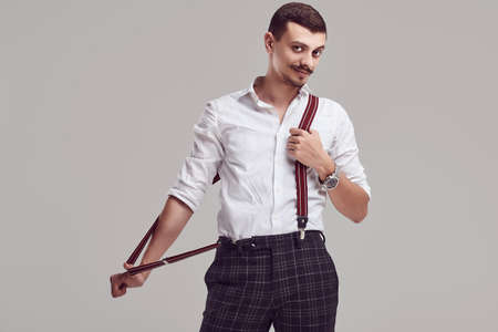 Portrait of handsome young confident arabic hipster with fancy mustache wearing white shirt and suspenders on gray studio background