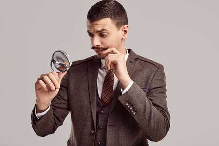 Portrait of handsome young confident arabic businessman with fancy mustache in woolen brown full suit looking in a small mirror on studio background