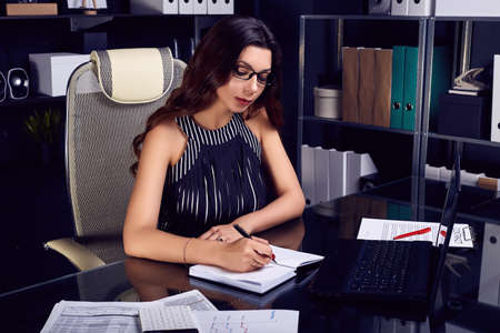 Portrait of young beautiful business woman in fashion suit and glasses working at stylish black computer desk