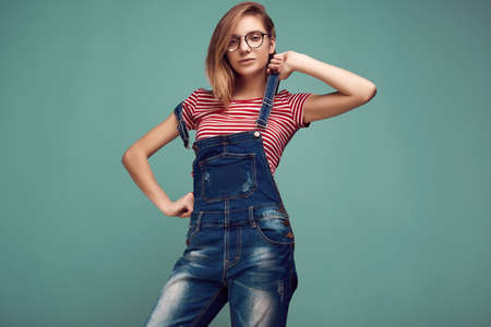 Portrait of cute teenage girl in denim overalls and glasses posing on color background. Studio shoot. Stock fotó
