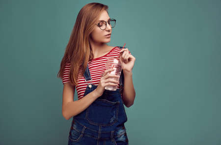 Portrait of cute teenage girl in denim overalls and glasses with soda water posing on color background. Studio shoot.