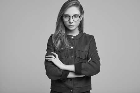 Portrait of cute teenage girl in fashion jacket and glasses posing on gray background. Studio shoot.