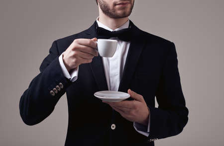 Fashion portrait of handsome elegant man with curly hair wearing tuxedo holding a cup of espresso on gray background in studio