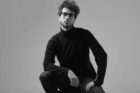 Fashion portrait of handsome elegant man with curly hair wearing black turtleneck and glasses on gray background in studio