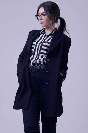 Portrait of fashion brunette woman wearing a striped blouse and black jacket isolated on white background in studio