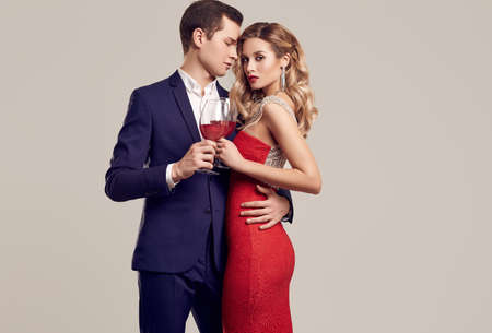 c1ee70b8c86e Portrait of sensual beautiful young couple dressed in formal clothes: woman  in fashion luxury red
