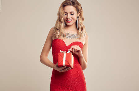 Portrait of gorgeous elegant sensual blonde woman wearing fashion red dress holding a wrapped gift isolated on white background Banque d'images