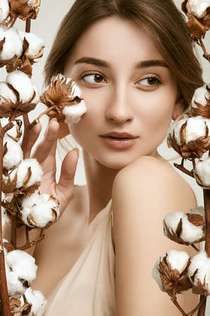 Sensual portrait of glamor woman model with clean skin posing among cotton twigs on white background in studio Banco de Imagens - 121938924
