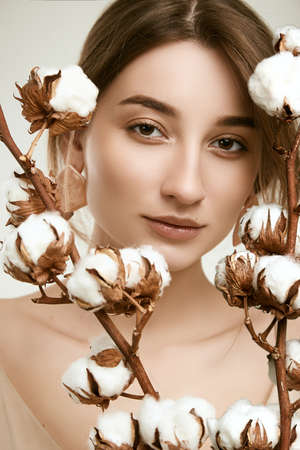 Sensual portrait of glamor woman model with clean skin posing among cotton twigs on white background in studio