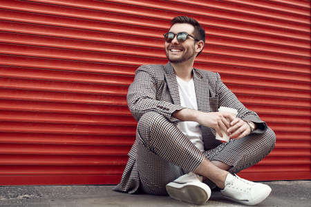 Portrait of young handsome brutal man in a fashion suit and sunglasses with cup of coffee sitting next to the red metal gate. Banque d'images
