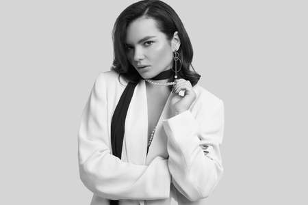 Studio portrait of attractive elegant caucasian woman with dark hair in fashion white suit isolated on light background Banco de Imagens
