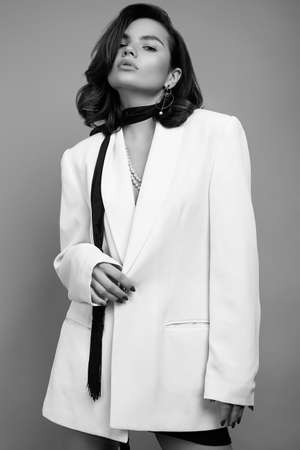 Studio portrait of attractive elegant caucasian woman with dark hair in fashion white suit