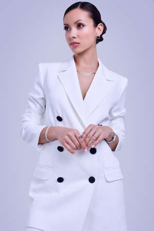 Portrait of a cute and gorgeous latin women in fashion white suit posing on bright studio background Banco de Imagens