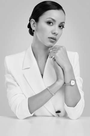 Portrait of a cute and gorgeous latin women in fashion white suit wearing expensive jewelry posing on bright studio background Banco de Imagens