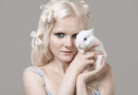 Fashion portrait of albino blond girl with white skin and blue eyes in elegant dress posing with cute little rabbit on gray background in studio