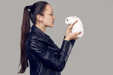 Portrait of gorgeous latin women in fashion leather jaket with cute little rabbit on gray studio background Фото со стока
