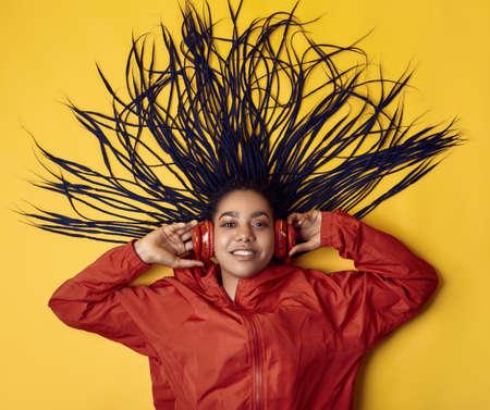 Portrait of beautiful african brunette teenage girl with dreadlocks wearing a red windbreaker listening music via wireless headphones isolated on vivid studio background Archivio Fotografico