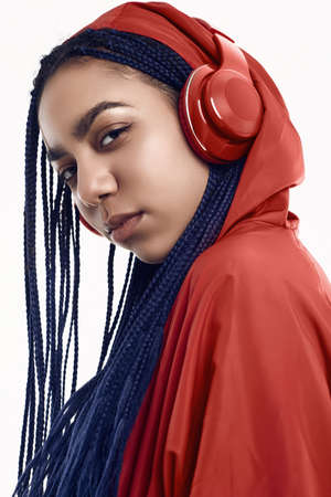 Portrait of beautiful african brunette teenage girl with dreadlocks wearing a red windbreaker listening music via wireless headphones isolated on studio background