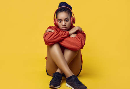 Portrait of beautiful african brunette teenage girl with dreadlocks wearing a red windbreaker listening music via wireless headphones isolated on vivid studio background 免版税图像