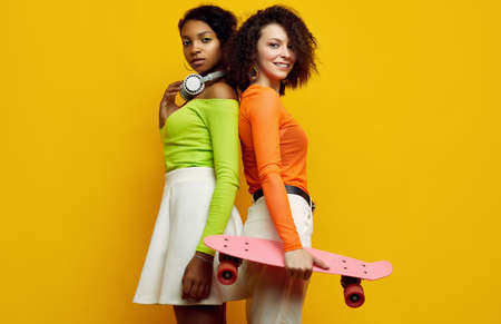 Portrait of two young beautiful hipster girls in trendy colorful summer clothes on yellow background. Crazy positive bright teens