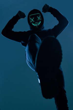 Retrato de un hombre anónimo con una sudadera con capucha negra que oculta su rostro detrás de una aterradora máscara de neón. Tiro del estudio. Ángulo inferior Foto de archivo