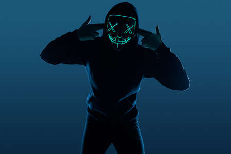 Portrait of an anonymous man in a black hoodie hiding his face behind a scary neon mask. Studio shot. Lower angle