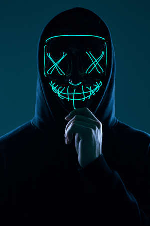 Portrait of an anonymous man in a black hoodie hiding his face behind a scary neon mask. Studio shot.