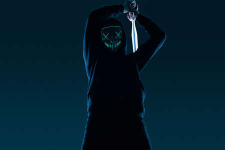Portrait of an anonymous criminal man with baseball bat in a black hoodie hiding his face behind a neon mask. Lower angle