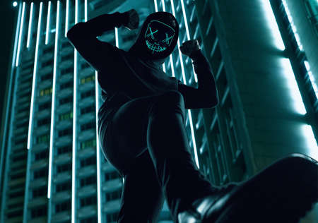 Portrait of an anonymous man in a black hoodie hiding his face behind a scary neon mask. Bright city background. Lower angle