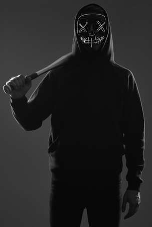 Portrait of an anonymous criminal man with baseball bat in a black hoodie hiding his face behind a neon mask. Studio shot.