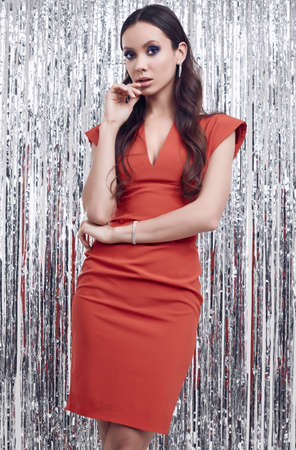 Portrait of gorgeous elegant hispanic brunette woman in luxurious red dress posing on silver shiny tinsel background. Studio shot.