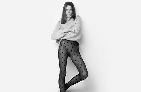 Studioporträt von fröhlichem Mode-Hipster-Mädchen in gemütlichem Pullover und schwarzen Strumpfhosen isoliert auf weißem Hintergrund