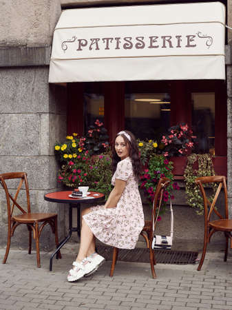 Portrait of a young beautiful bright girl in a summer dress sitting at a European cafe table with a cup of coffee and dessert.