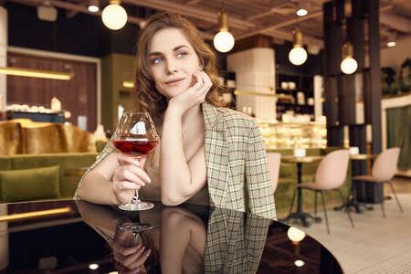 Portrait of elegant beautiful brunette woman with glass of red wine in restaurant interior 版權商用圖片