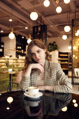 Portrait of confident young businesswoman in smart casual wear drinks coffee in a cafe interior
