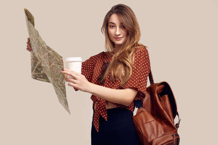 Travel concept. Dreaming about journey. Studio portrait of pretty young hipster woman with backpack holding map. Isolated on gray background