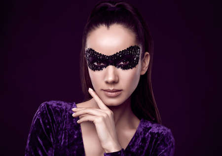 Portrait of charming elegant brunette woman in beautiful purple dress and sequins mask posing on black background in studio Banque d'images