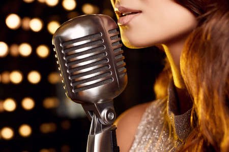 Close-up portrait of gorgeous singer woman in elegant dress with retro microphone on restaurant stage spotlights background.