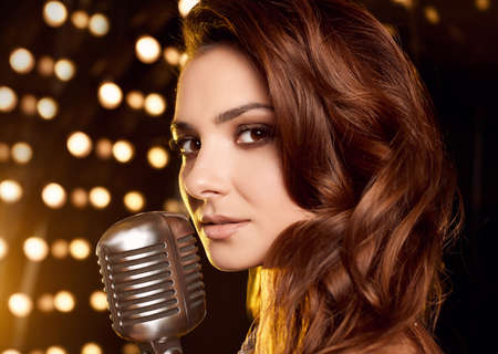 Close-up portrait of gorgeous singer woman in elegant dress with retro microphone on restaurant stage spotlights background. Stock Photo