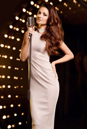 Portrait of gorgeous singer woman in elegant dress with retro microphone on restaurant stage spotlights background. Stock fotó