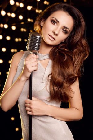 Portrait of gorgeous singer woman in elegant dress with retro microphone on restaurant stage spotlights background.