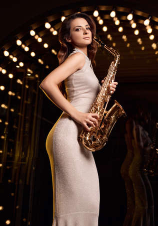 Portrait of gorgeous brunette model woman in elegant dress with saxophone playing on restaurant stage spotlights background.