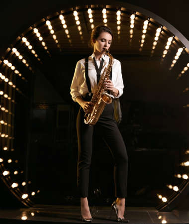 Portrait of gorgeous brunette model woman in fashionable formal suit with saxophone playing on restaurant stage spotlights background.