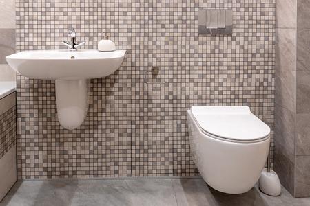 Umywalka i zabudowana toaleta w nowoczesnej łazience. Zdjęcie Seryjne
