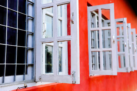 open windows: Open white windows on an unevenly painted red wall Stock Photo