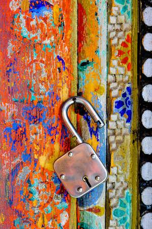 unlocked: An unlocked lock hanging on the colorful wall of Buddhist monastary in Ladakh