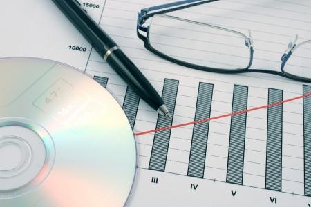 ballpoint pen, cd and glasses on earning graphs photo