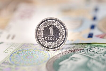 One zloty coin on Polish currency banknotes business background